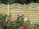 Garden fence with concrete gravelboards and wooden posts, with trellis top.